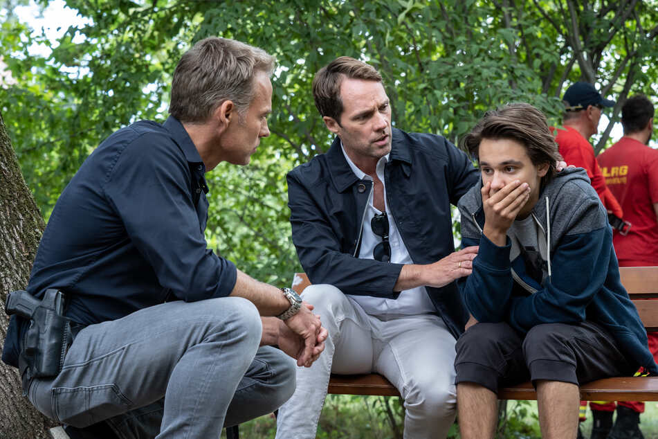 Joscha (r.) hat beim Angeln eine Leiche gefunden. Sein Vater Marcus (M.) und Ermittler Jan Maybach kümmern sich um den geschockten Teenager.
