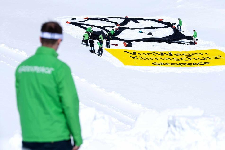 """Aktivisten von Greenpeace haben auf dem Gletscher an der Zugspitze ein VW-Logo und ein Banner mit der Aufschrift """"VonWegen Klimaschutz"""" ausgerollt."""