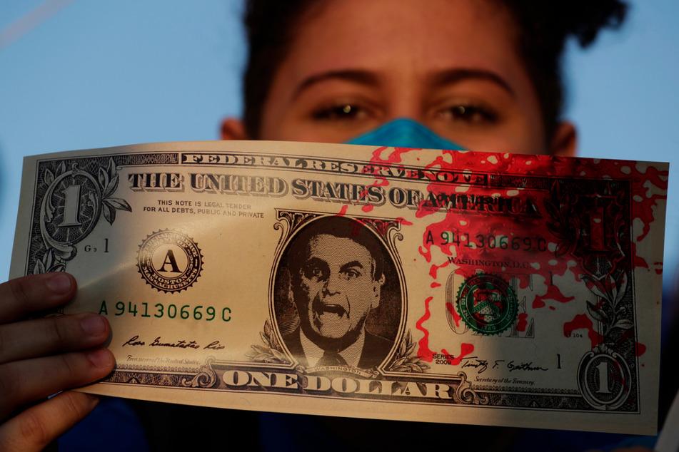 Eine Frau hält eine Kopie eines US-Dollar-Scheins, auf dem ein Bild des brasilianischen Präsidenten Jair Bolsonaro sowie rote Farbe, die das Blut von Covid-19-Opfern symbolisiert, zu sehen ist.