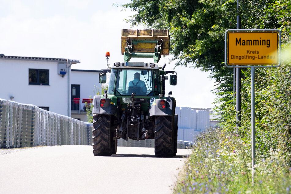 Ein Landwirt fährt mit seinem Traktor am Ortsschild von Mamming und einer Konservenfabrik entlang.