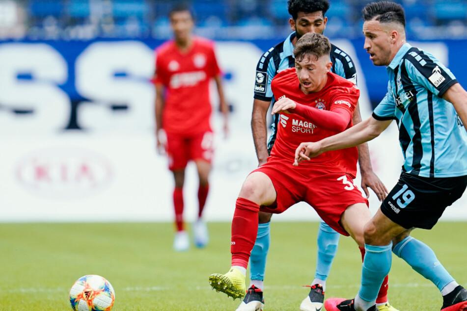 Münchens Angelo Stiller (Vordergrund, rotes Trikot) kämpft mit den Mannheimern Mounir Bouziane und Mohamed Gouaida um den Ball.