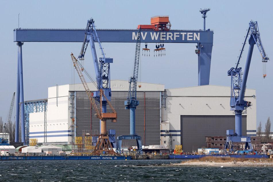 """Der Standort Warnemünde der MV Werften mit dem Bockkran und der Aufschrift """"MV Werften""""."""