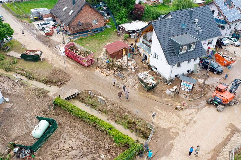 Bei einem Unwetter in der Nacht zu Samstag liefen in Hennef Angaben der Feuerwehr zahlreiche Keller voll und Hänge rutschten ab. Anwohner entsorgen anschließend zerstörte Gegenstände aus ihren Häusern.