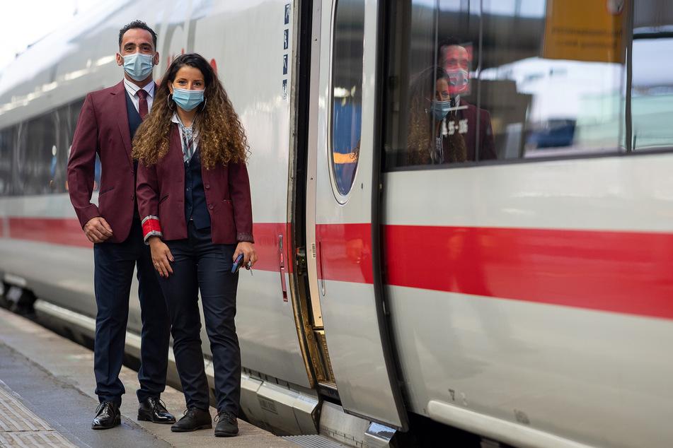 Zwei Zugbegleiter stehen in der Bekleidung der Deutsche Bahn neben einem ICE.