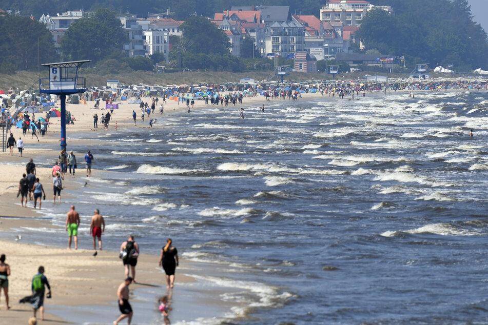 Touristen spazieren am Strand an der Ostsee auf der Insel Usedom entlang. Millionen Urlauber in Deutschland fahren jedes Jahr ans Meer.