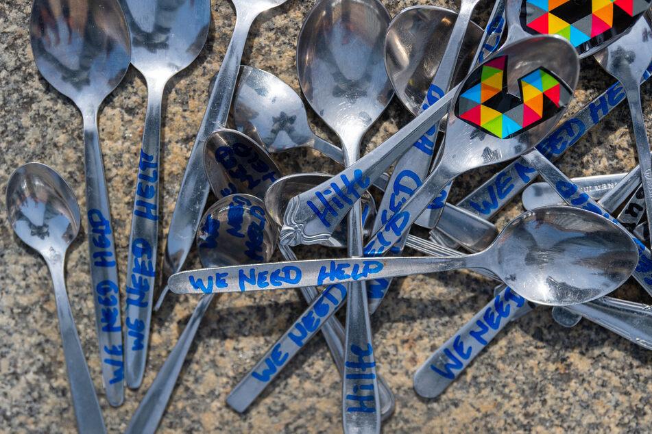 """Löffel mit der Aufschrift: """"We need help"""" und """"Hilfe""""."""