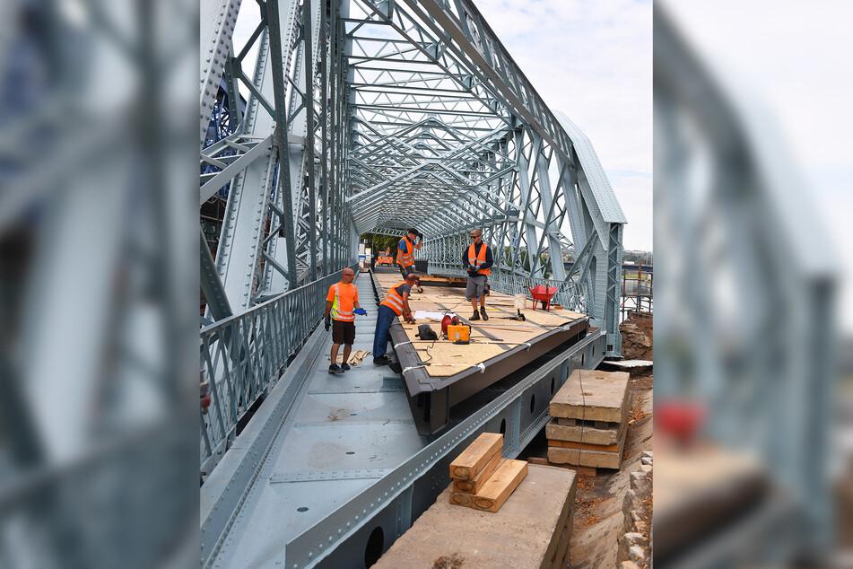 Die Arbeiter montieren derzeit die letzten Teile der neuen Fahrbahn auf der Brücke.
