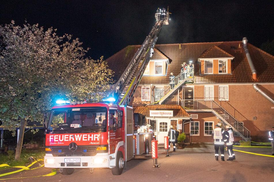 Feuerwehrleute löschen die brennende Wohnung im zweiten Obergeschoss.