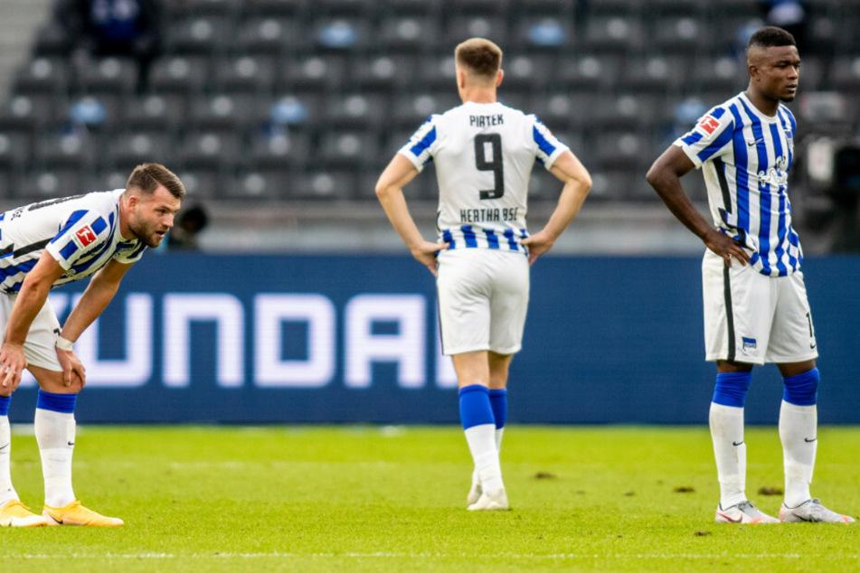 Herthas Eduard Löwen (l.), Krzysztof Piatek und Jhon Cordoba (r.) von Hertha BSC stehen nach der Niederlage enttäuscht auf dem Spielfeld.
