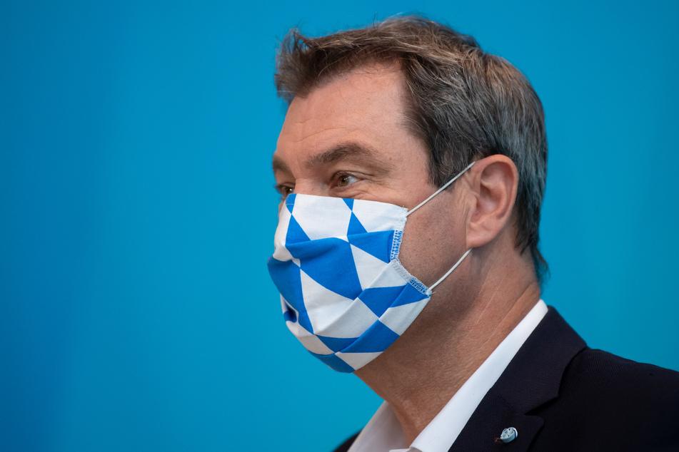 Markus Söder (CSU), Ministerpräsident von Bayern, trägt einen Mundschutz in den bayerischen Landesfarben.