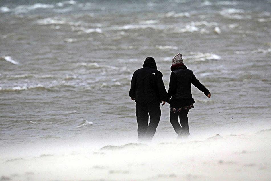Zwei Urlauber gehen bei Sturm am Strand spazieren. (Archivbild)