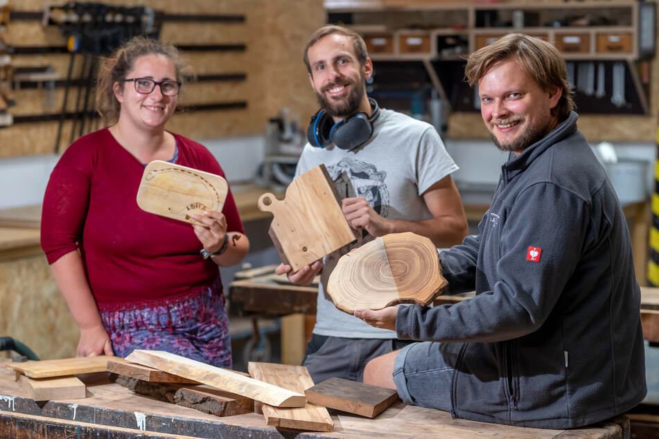 Caroline Kügler (29), Jonas Titus Kerber (28) und Philipp Salzmann (32) vom Holzkombinat zeigen Frühstücksbrettchen aus Holz.
