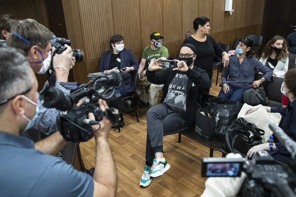 Kirill Serebrennikow (M), Theater- und Filmregisseur aus Russland, trägt einen Mundschutz mit einem Porträt des russischen Rocksängers Viktor Tsoi und fotografiert Medienvertreter vor seiner Anhörung in einem Gerichtssaal.