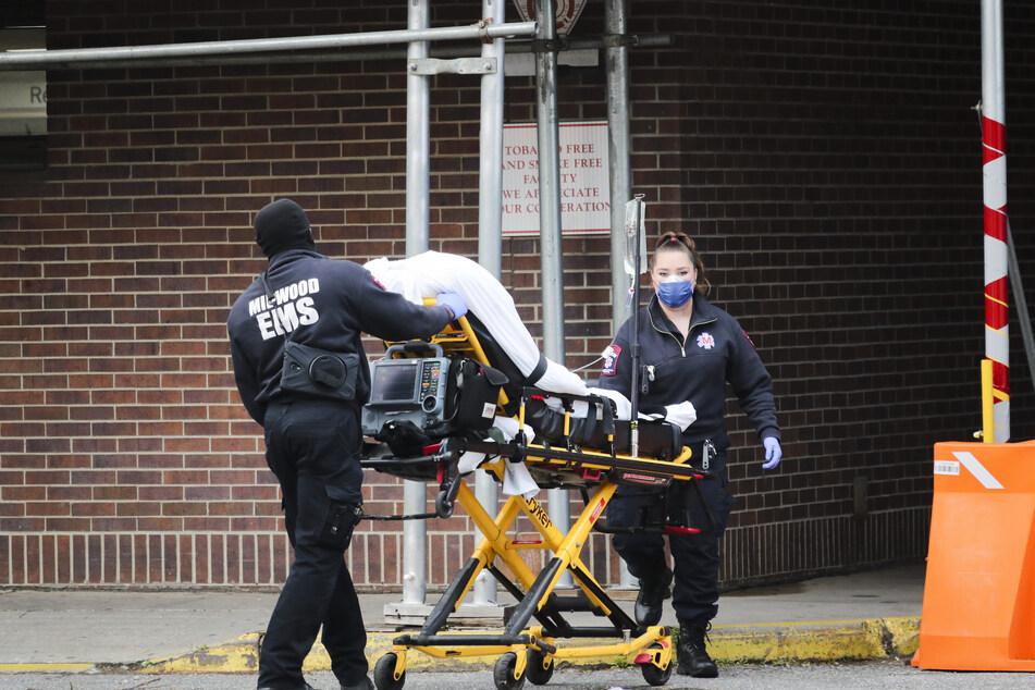 Mitarbeiter des Gesundheitswesens schieben einen Patienten in das Brooklyn Hospital Center in Brooklyn.