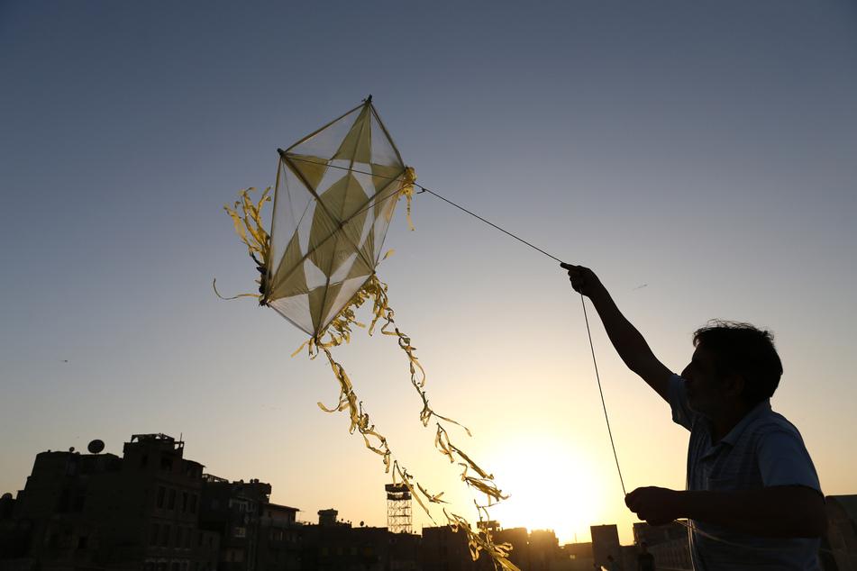 Kairo: Ein Mann lässt auf dem Dach eines Gebäudes einen Drachen steigen. Nach mehreren Unfällen mit Drachen in Kairo geht die ägyptische Regierung dort gegen Verkäufer der bei Kindern beliebten Spielgeräte vor.