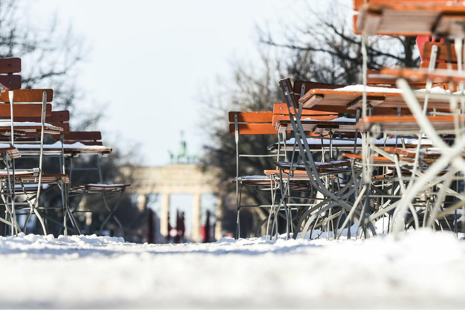 Stühle und Tische stehen im Schnee vor dem Brandenburger Tor.