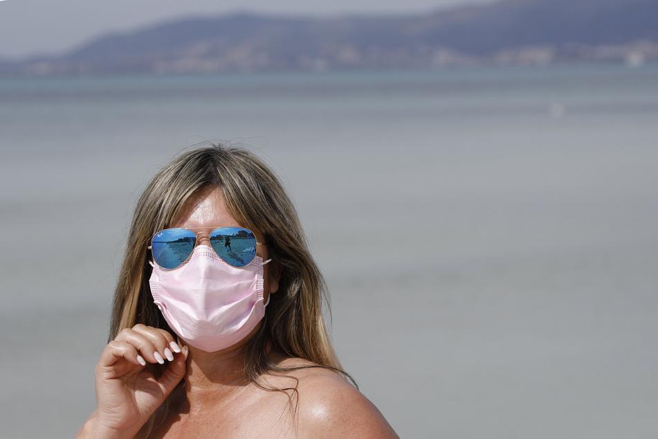 Spanien, Palma de Mallorca: Nadine aus Zürich trägt eine medizinische Maske, während sie die Sonne am Strand von El Arenal genießt.
