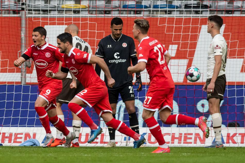 Freude und Enttäuschung eng beieinander: Die Düsseldorfer bejubeln den zweiten Treffer, St. Paulis Luca Zander (r.) ist konsterniert.