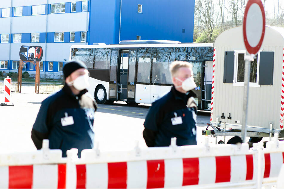 Schleswig-Holstein, Flensburg: Zwei Sicherheitsleute stehen vor der Einfahrt zu einer mobilen Abstrichstation. Im Hintergrund steht ein zur mobilen Abstrichstation modifizierter Omnibus auf einem Parkplatz. Hier können Menschen nach vorheriger Anmeldung für einen Corona-Schnelltest vorfahren.