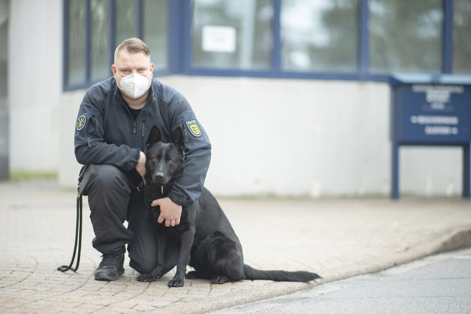 Diensthundeführer Florian Weiner steht mit seiner schwarzen Schäferhündin Emily vor dem Eingang des Gefängnisses in Heimsheim.