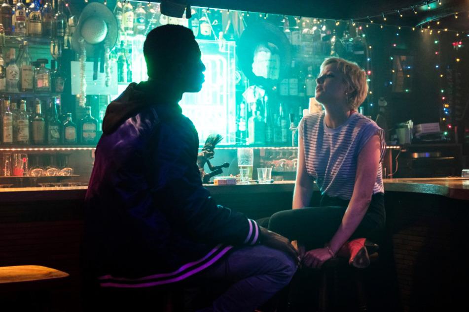 Francis (l., Welket Bungué) flirtet mit Mieze (Jella Haase) in einer Bar.