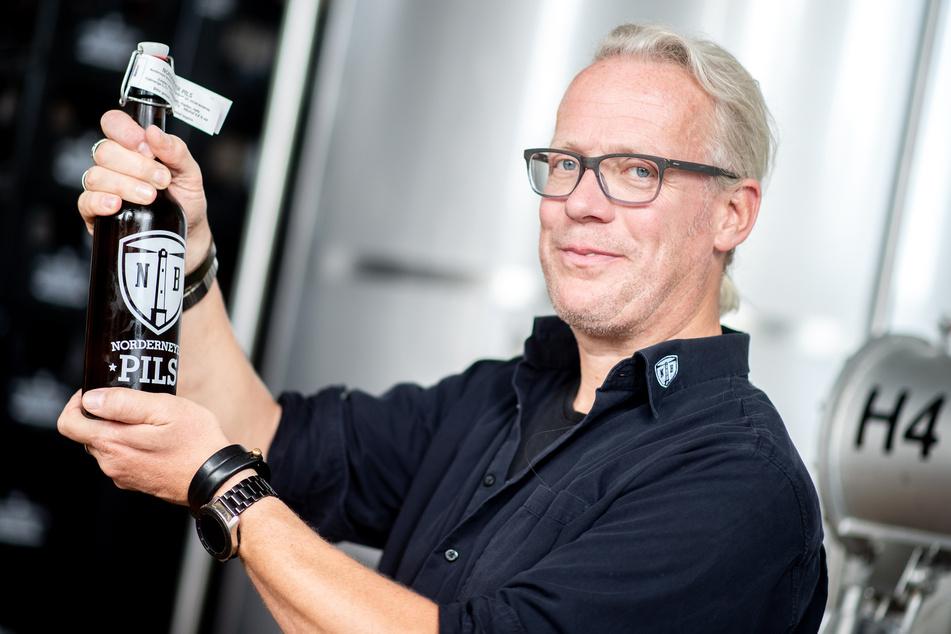 Tobias Pape, Geschäftsführer vom Norderneyer Brauhaus, hält in der Brauanlage auf der Insel eine Flasche Pils in den Händen. Nach dem Wahlsieg Joe Bidens in den USA hat der Brauer alle Insulaner über 16 Jahren zu einem Freibier eingeladen.