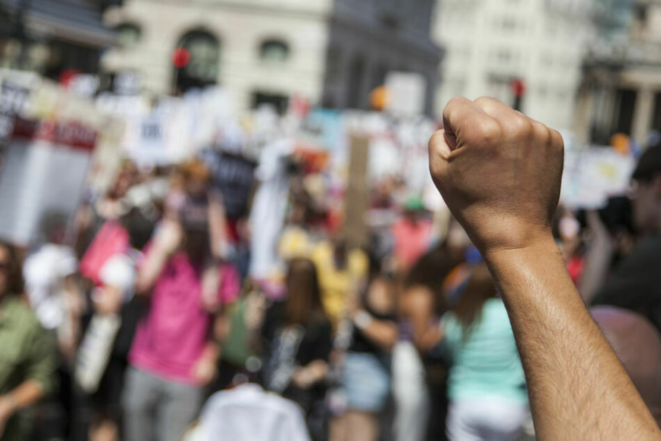 Eine Faust erstreckt sich in einer Demonstration. (Symbolbild)