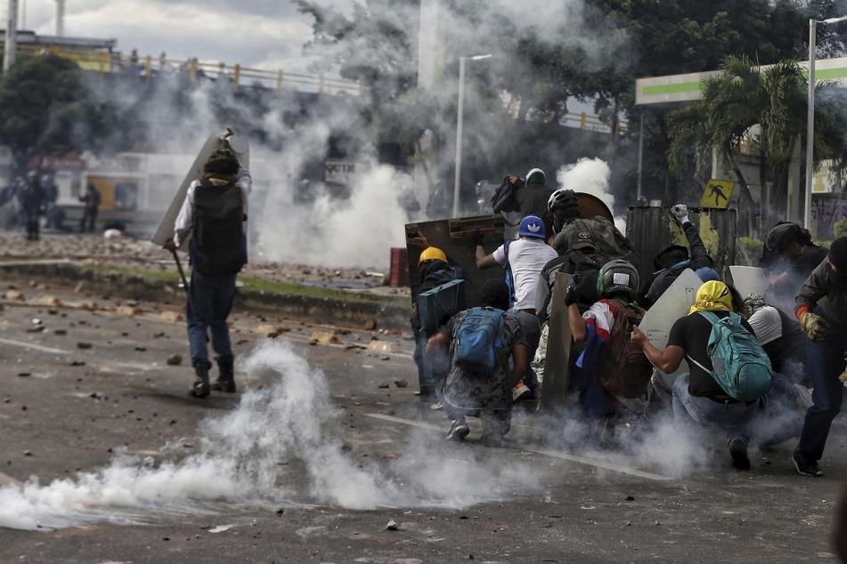 Demonstranten schützen sich vor Tränengas und Schüssen der Polizei. Die Gewalt hält an auf den Straßen Calis und in ganz Kolumbien.