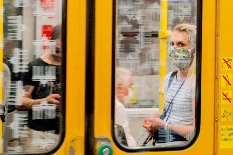 Eine Frau fährt mit Mundschutz in der U-Bahn.