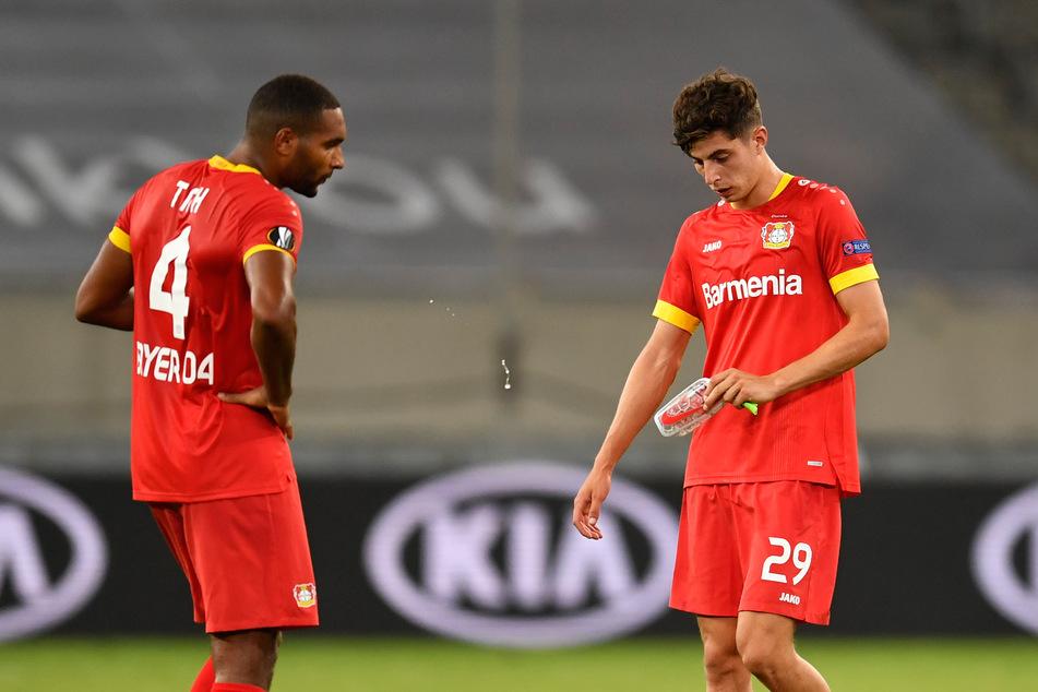 Leverkusens Jonathan Tah (l.) und Kai Havertz stehen nach Abpfiff enttäuscht auf dem Platz.
