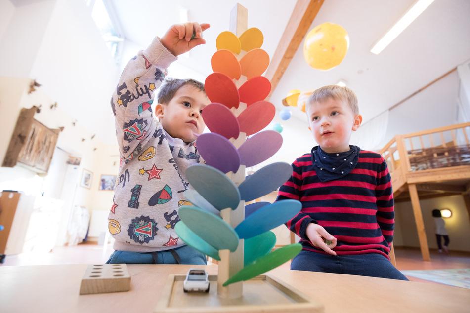 Kinder spielen in einem Kindergarten mit einer klingenden Murmelbahn.