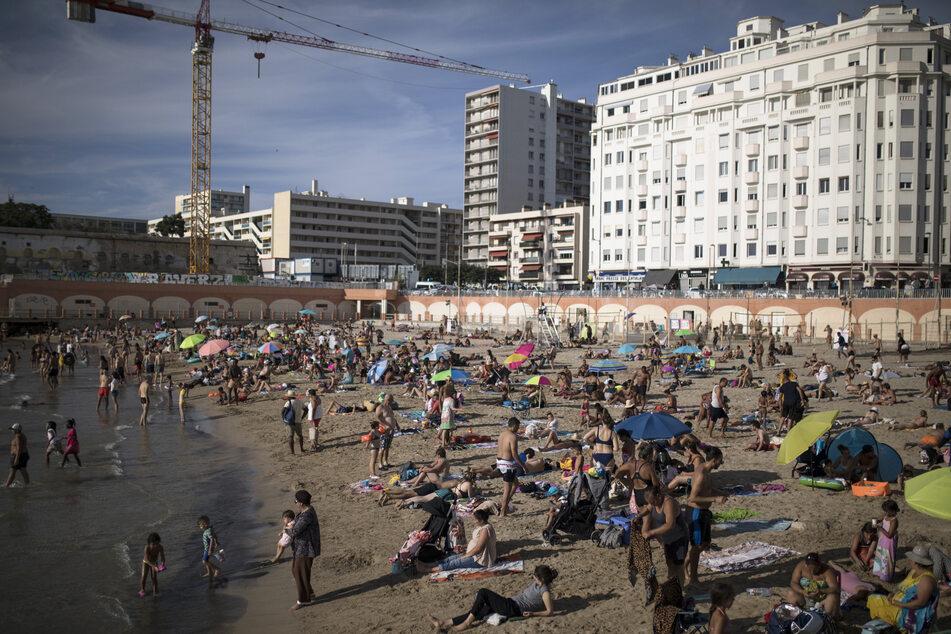 Strandbesucher genießen die Sonne am Plage des Catalans.