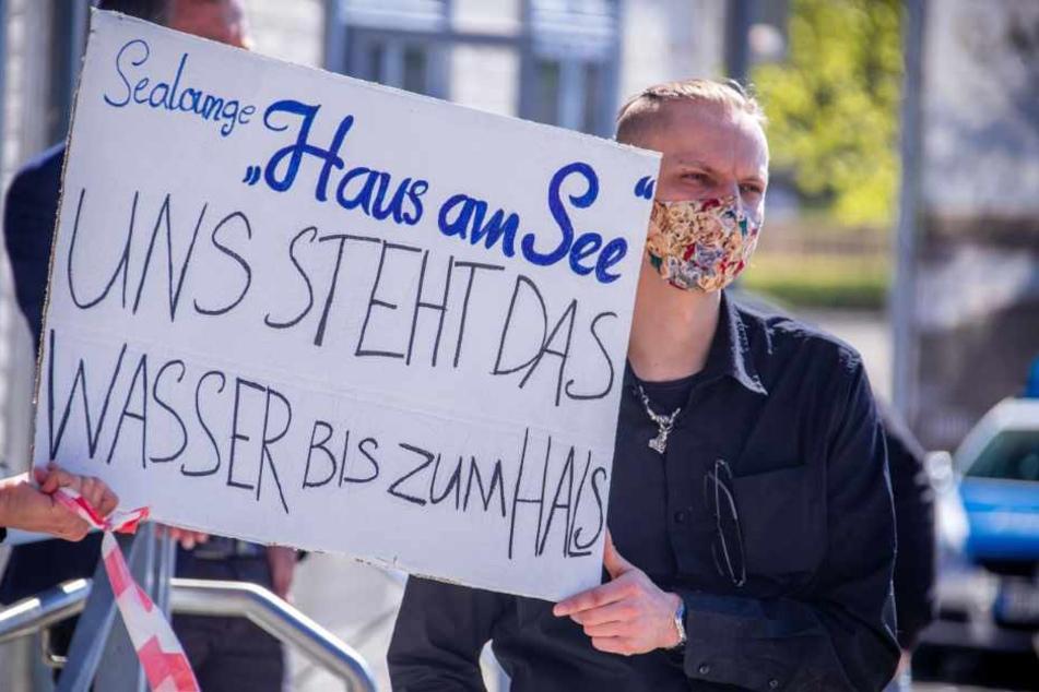 """Ein Demonstrant trägt bei einer Demonstration für finanzielle Hilfen und Steuererleichterungen zur Rettung der geschlossenen Betriebe im Tourismusgewerbe einen Mundschutz und ein Schild mit der Aufschrift """"Sealounge Haus am See - Uns steht das Wasser bis zum Hals""""."""