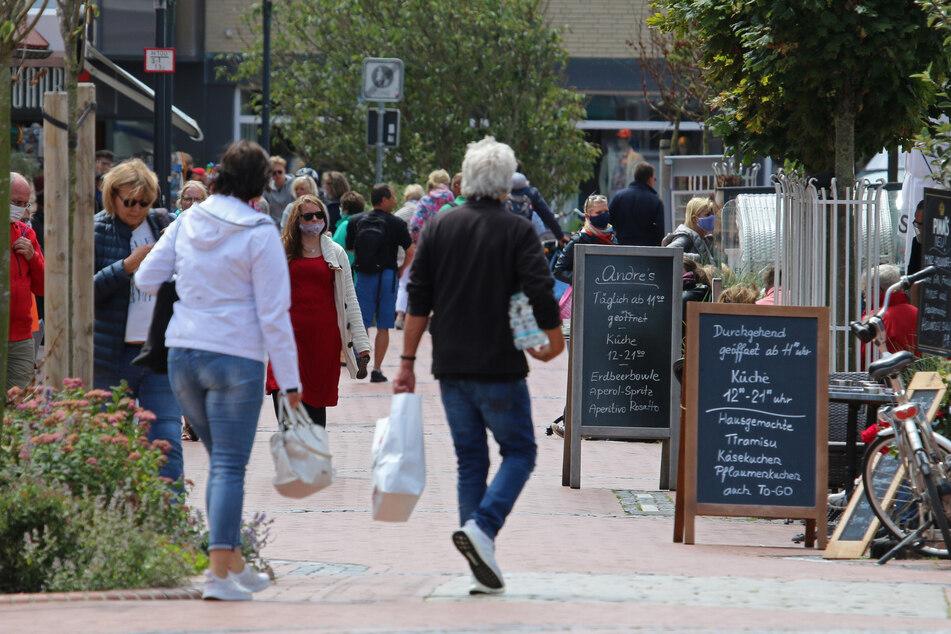 Urlauber gehen teils mit, teils ohne Gesichtsmaske durch die Friedrichstraße.