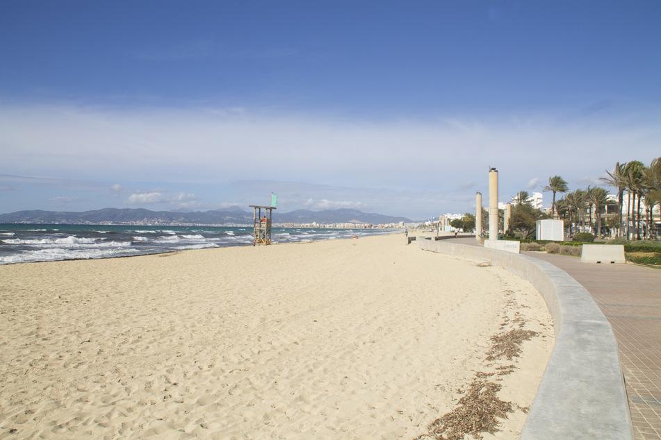Ein Bademeister (l) arbeitet am leeren Strand von Palma. Die Corona-Krise hat die deutsche Reisebranche weiter fest im Griff.