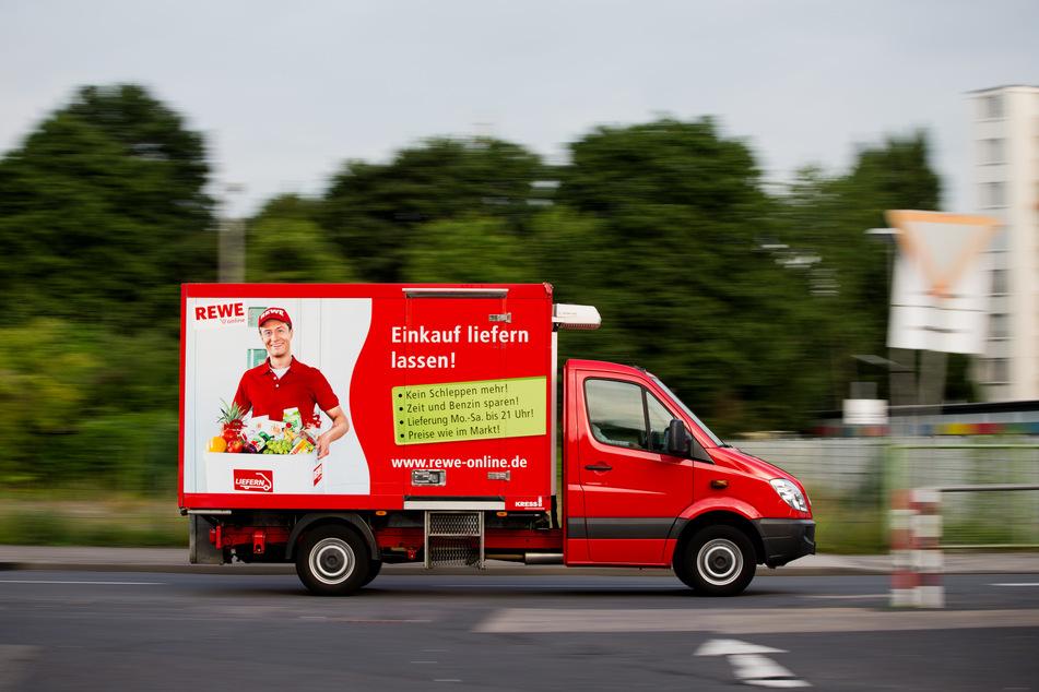 Ein Lieferwagen von Rewe Online fährt am auf einer Straße.