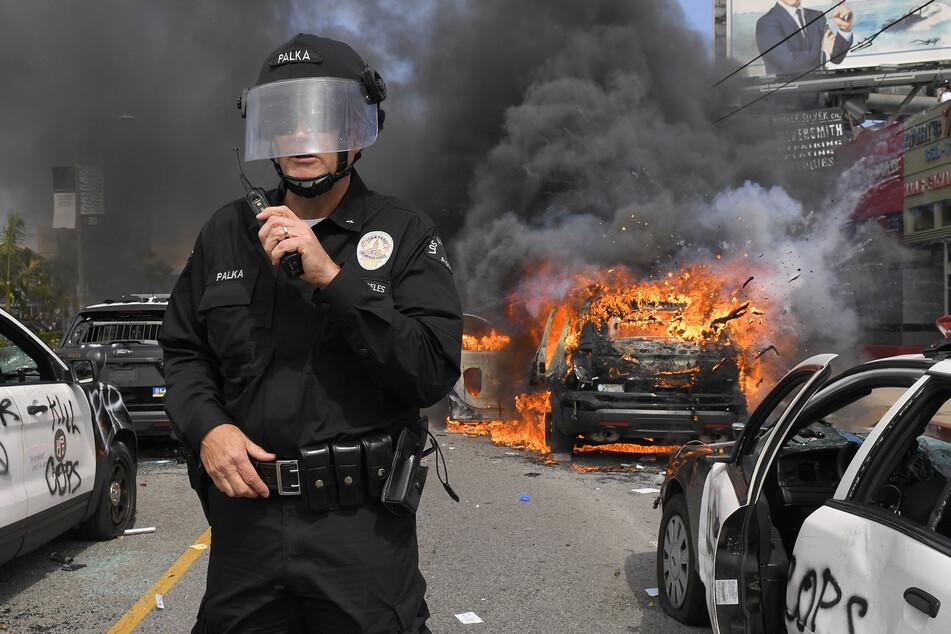 Los Angeles: Ein Kommandeur des Los Angeles Police Department, steht während eines Protests zwischen mehreren zerstörten, in Flammen stehenden Polizeiautos.
