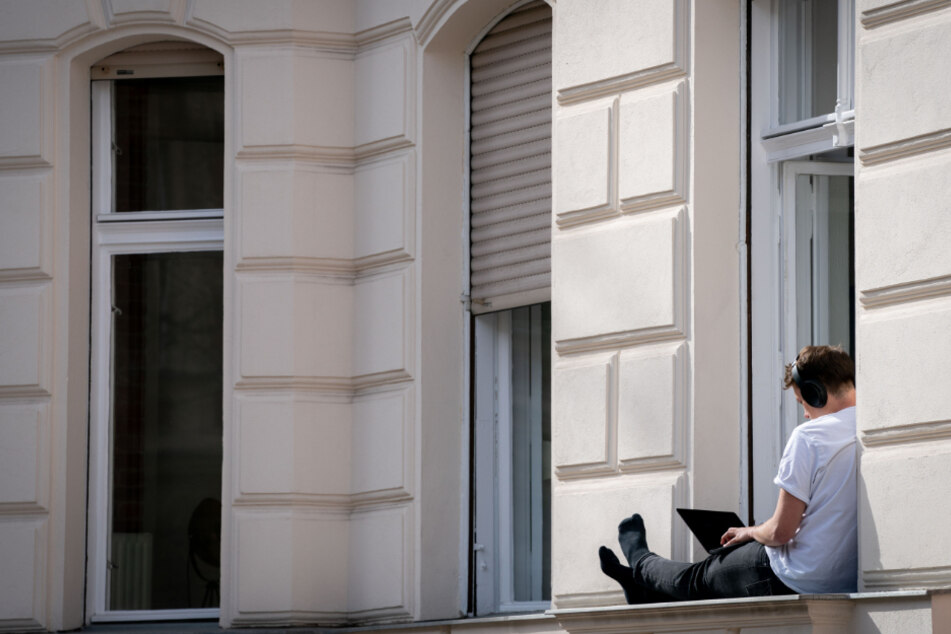 Ein Mann hat sein Homeoffice auf die sonnige Fensterbank seiner Wohnung verlegt.