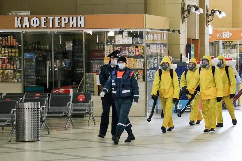 Mitarbeiter der Stadt in gelben Schutzanzügen desinfizieren den Bahnhof Kiewski (Kiew) in Moskau.