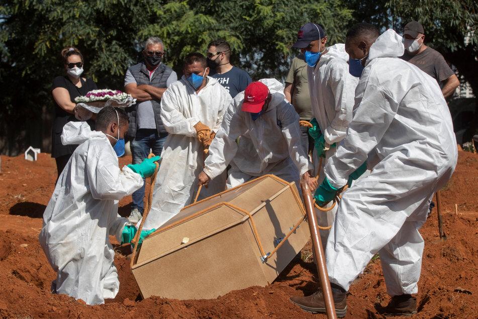 São Paulo: Friedhofsarbeiter in voller Schutzausrüstung tragen auf dem Friedhof Vila Formosa einen Sarg, der die Überreste einer Person enthält, die an Komplikationen im Zusammenhang mit Covid-19 gestorben ist.