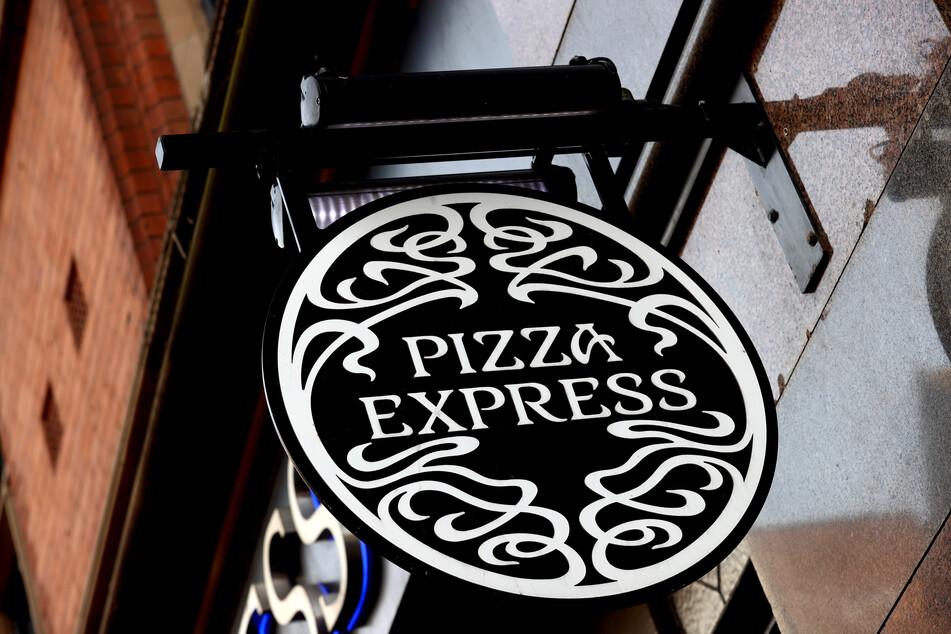 Ein Schild mit dem Logo von Pizza-Express hängt an einem Restaurant.