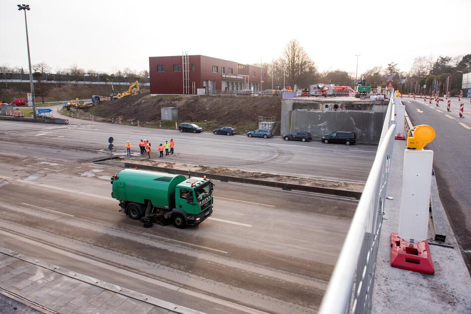 Eine Kehrmaschine säubert die Fahrbahn unter einer teilweise abgerissenen Brücke über die Autobahn A7 an der Abfahrt Othmarschen.