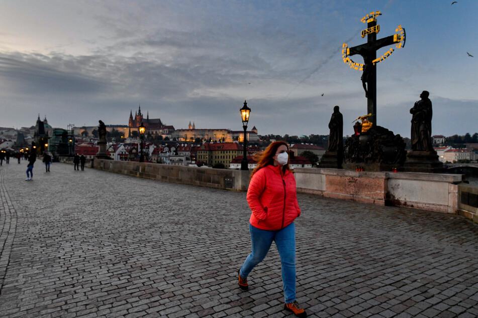 Eine Frau mit Mund-Nasen-Schutz geht über die Prager Karlsbrücke. In Tschechien gelten strenge Ausgangsbeschränkungen. Die Menschen sind angehalten, so weit wie möglich zu Hause zu bleiben. Restaurants müssen geschlossen bleiben.