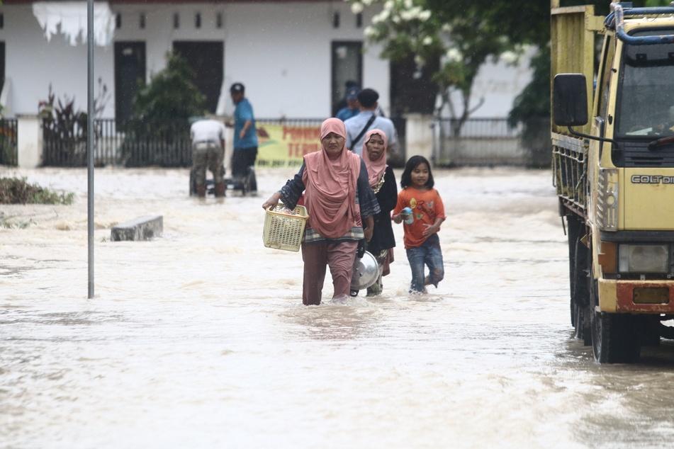 Anwohnerinnen waten nach einer Sturzflut mit ihren Habseligkeiten durch das Wasser auf einer überschwemmten Straße in der Provinz Süd-Sulawesi.