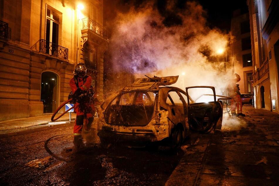 Feuerwehrmänner löschen ein brennendes Auto in der Nähe der Champs-Elysées. Nach dem Sieg der Bayern über PSG hatten französische Fußballfans in Paris randaliert.