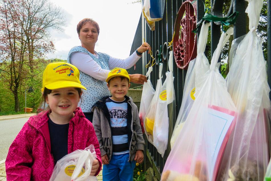 Kita-Leiterin Sylvia Weißflog (42) hängt Kreativmappen-Beutel an den Zaun. Johanna und Paul freuen sich auf Gedichte, Malvorlagen und Basteleien für Zuhause.