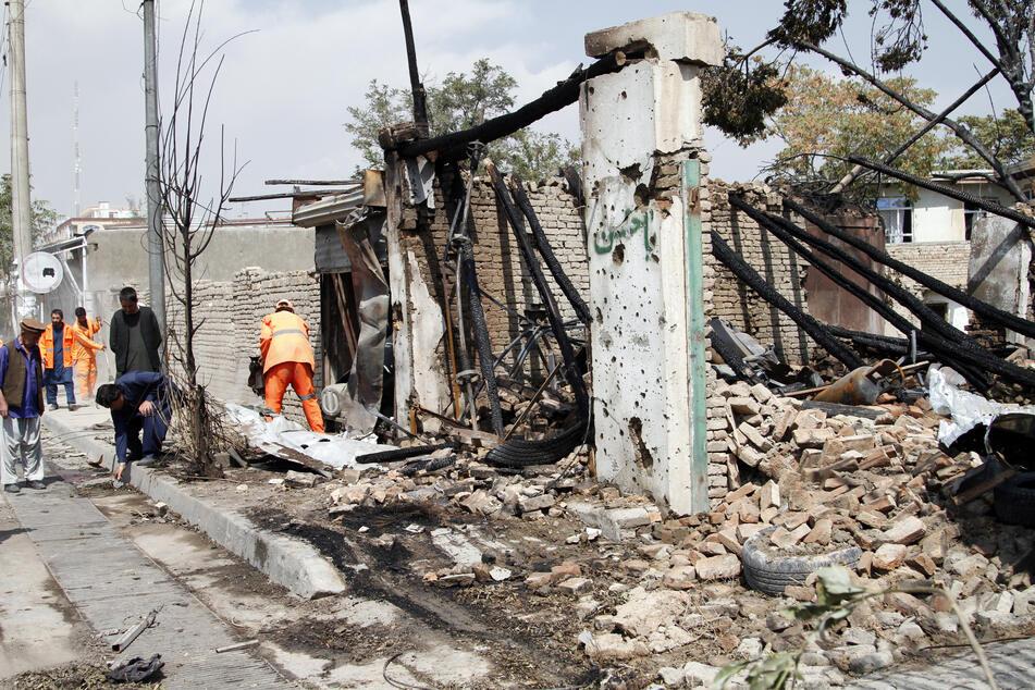 Afghanische Sicherheitskräfte und Mitarbeiter der Stadtverwaltung reinigen den Ort der Explosion.