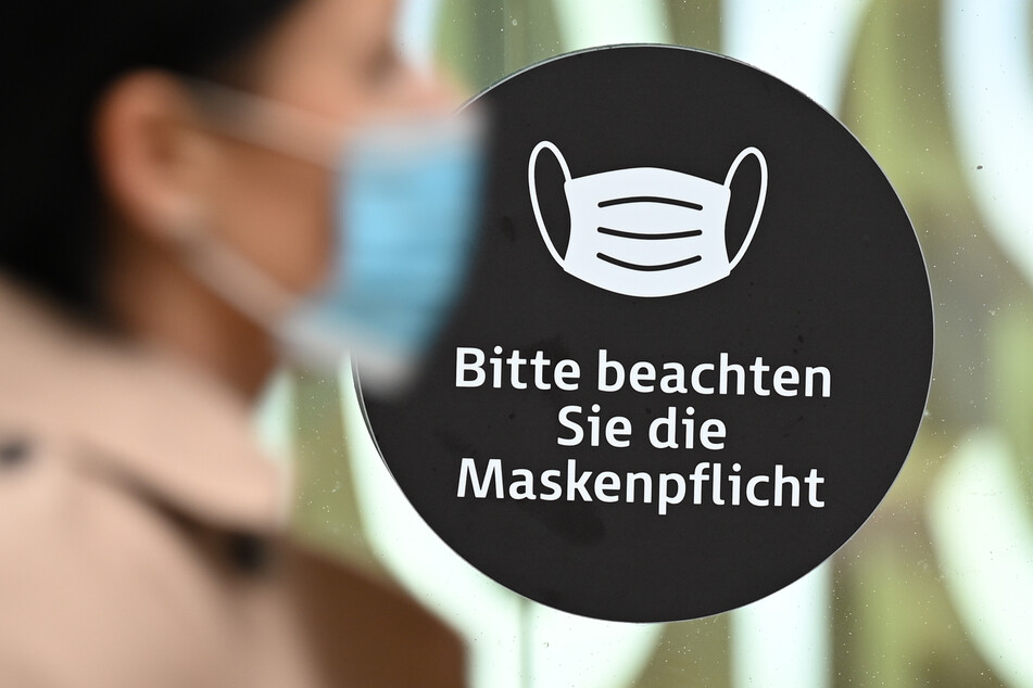 """Eine Frau, die einen Mund-Nasen-Schutz trägt, geht auf der Frankfurter Einkaufsmeile Zeil an einem Aufkleber an einer Schaufensterscheibe mit der Aufschrift """"Bitte beachten Sie die Maskenpflicht"""" vorbei."""