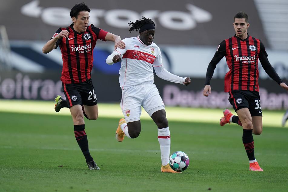 Eintracht Frankfurts André Silva (r.) beobachtet, wie Teamkollege Makoto Hasebe (l.) versucht Tanguy Coulibaly vom VfB Stuttgart zu stoppen.