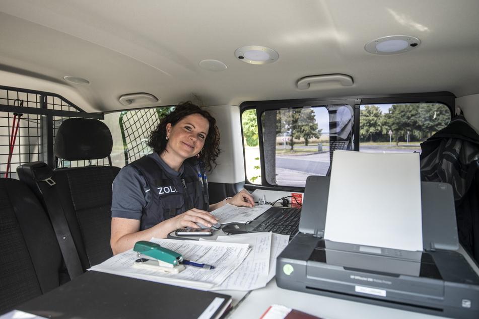 Eine Zoll-Beamtin kontrolliert in einem Wagen die Angaben der Fahrer.